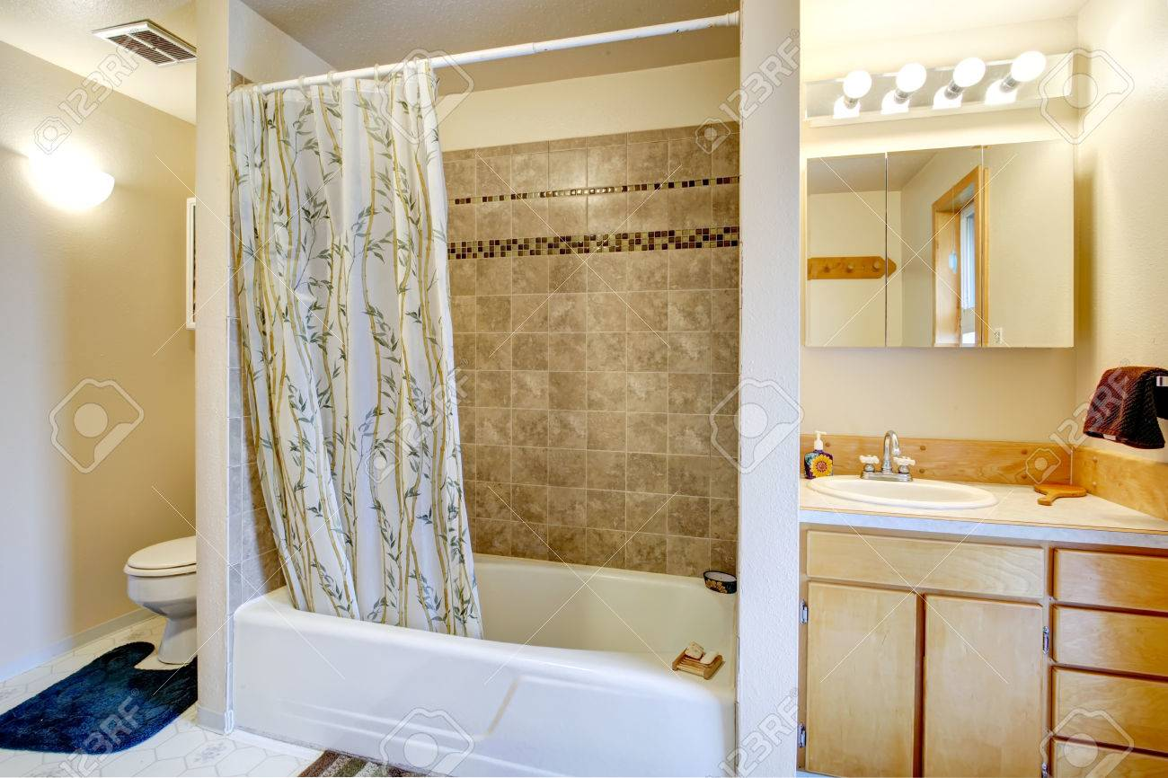 archivio fotografico vista della vasca da bagno con tende e muro di piastrelle trim vanity con specchio e wc con la coperta blu