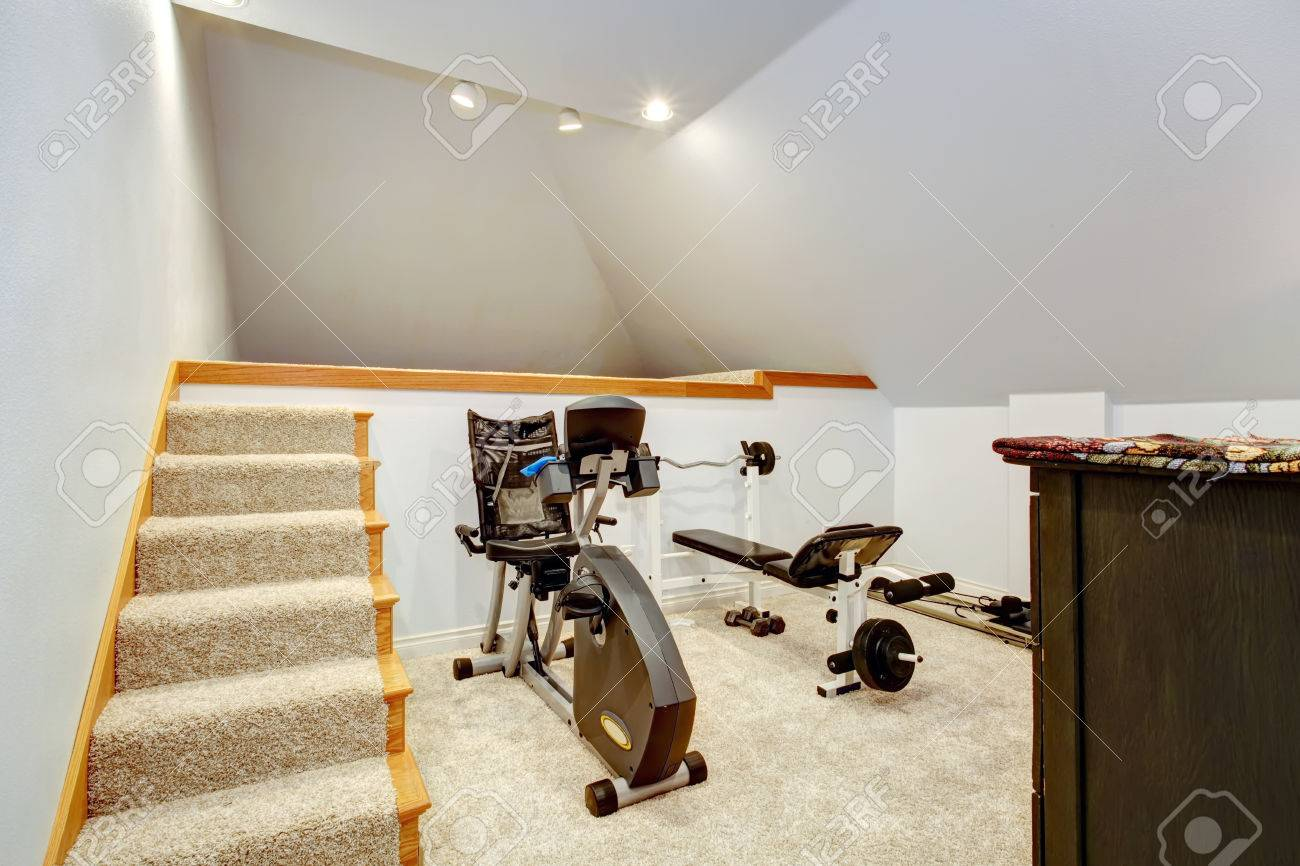 Small home gym with two exercise equipments and stairs stock photo