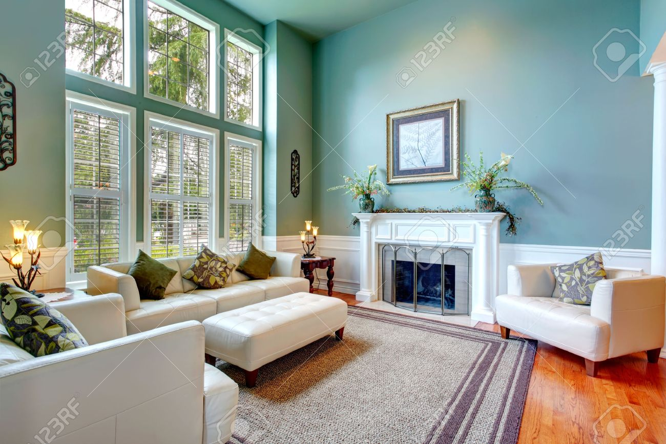 High Ceiling Aqua Living Room With White Leather Couch, Ottaman, Armchairs  And Fireplace Stock