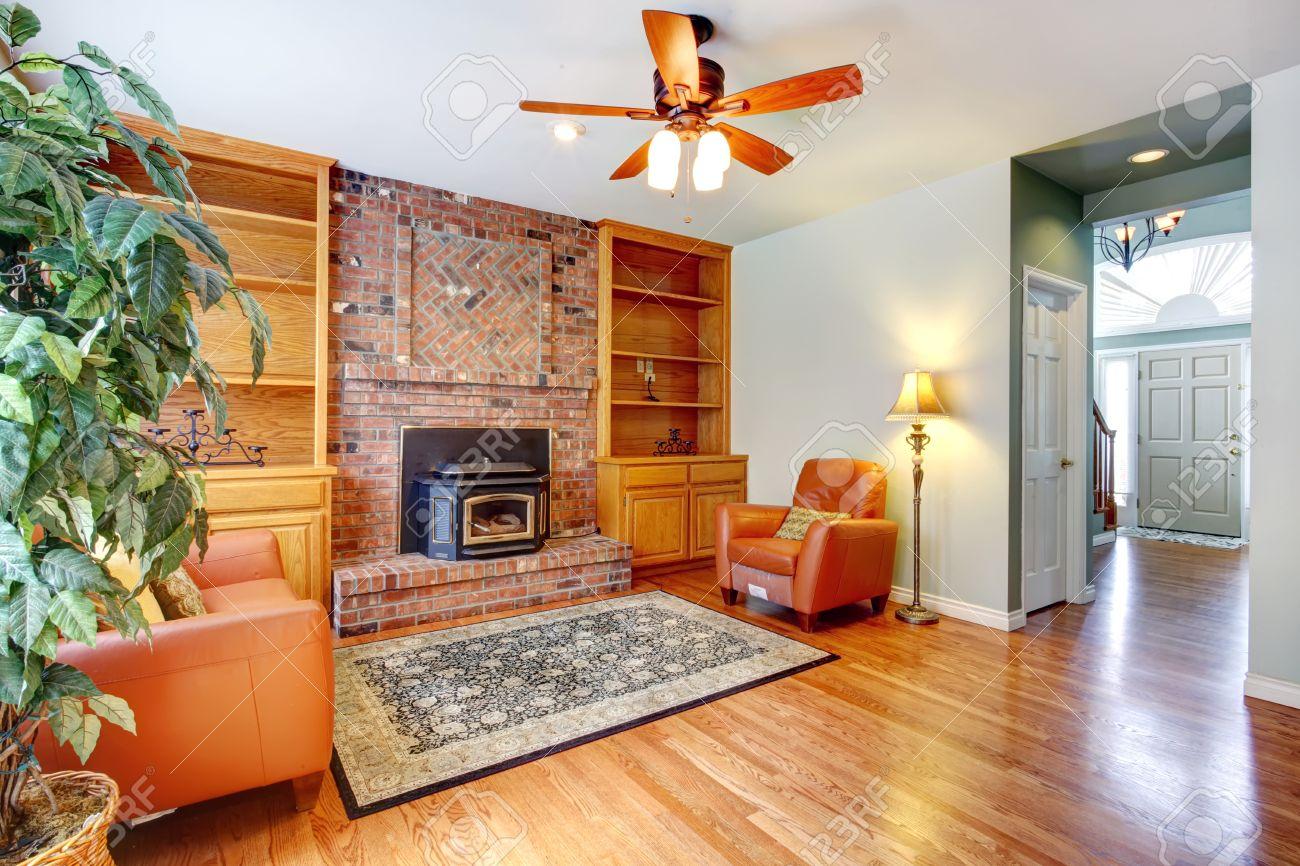 Salon avec cheminée de briques et poêle antique vue de fauteuils ...