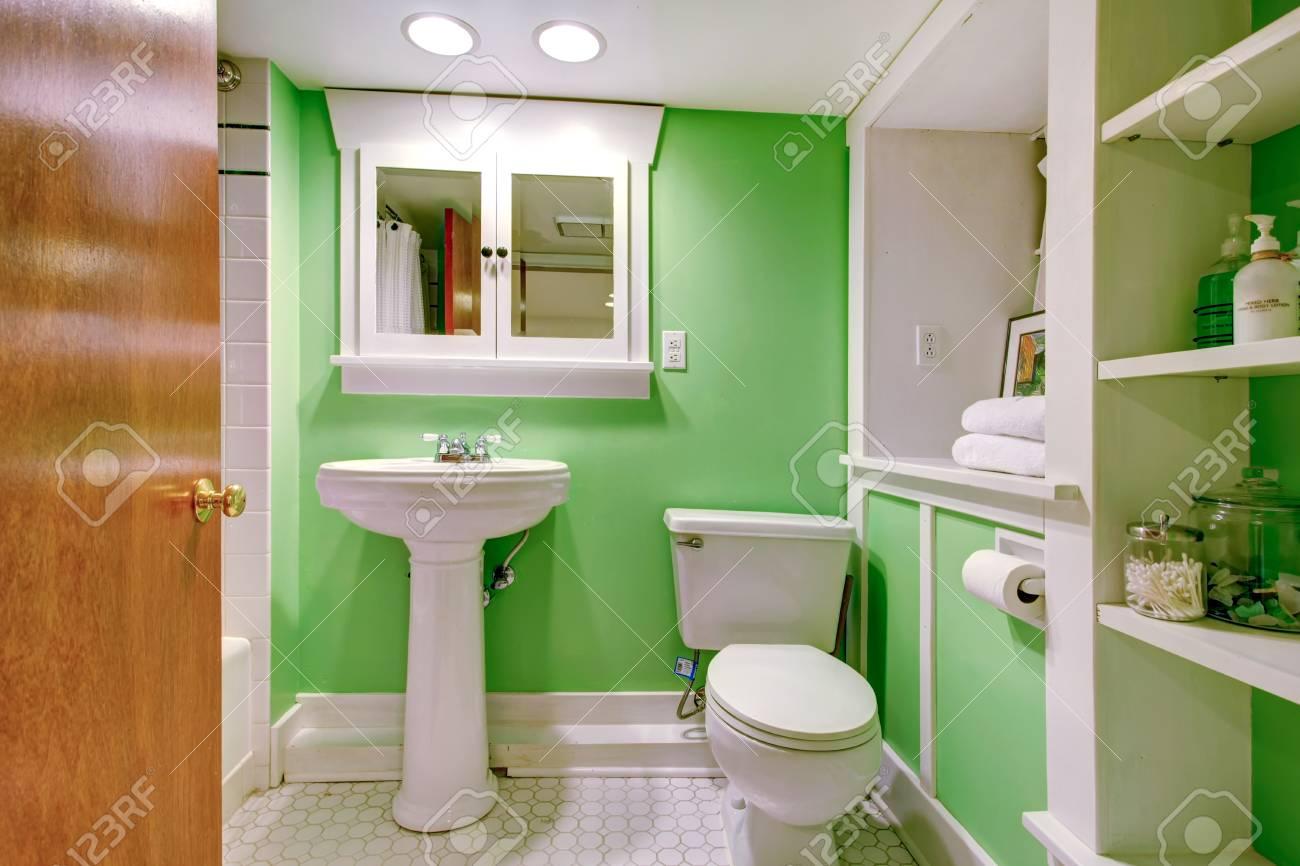 Salle de bains intérieur perfeclty mur vert de mélange avec meuble de  rangement blanc et lavabo blanc debout avec WC