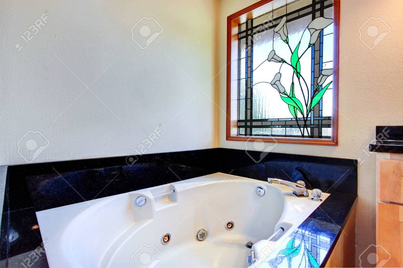 Bathroom With White Whirlpool Tub, Black Tile Trim Around It And Stained  Glass Window Stock