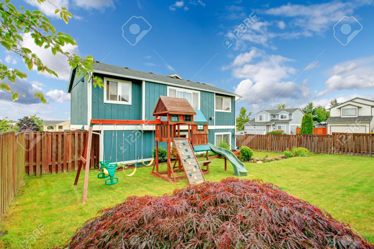 small fenced backyard with playground for kids with chute swings