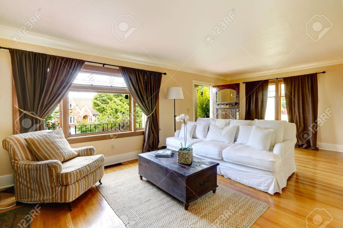 Ivory Living Room With Curtained Windows, Hardwood Floor Room Furnished  With White Comfortable Sofa,