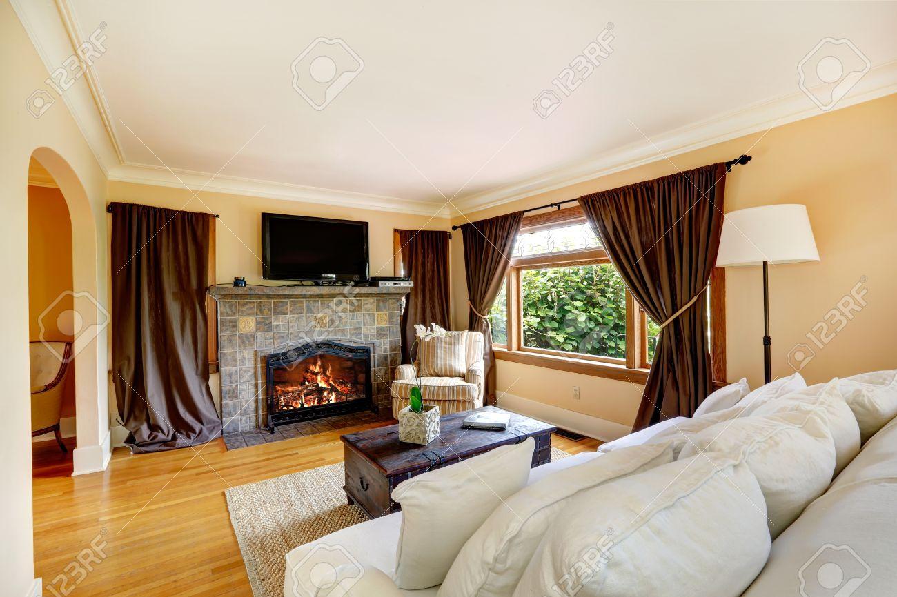 Ivoire salon avec des fenêtres à rideaux, cheminée en pierre de fond et le  plancher de bois franc chambre meublée avec un canapé blanc confortable, ...