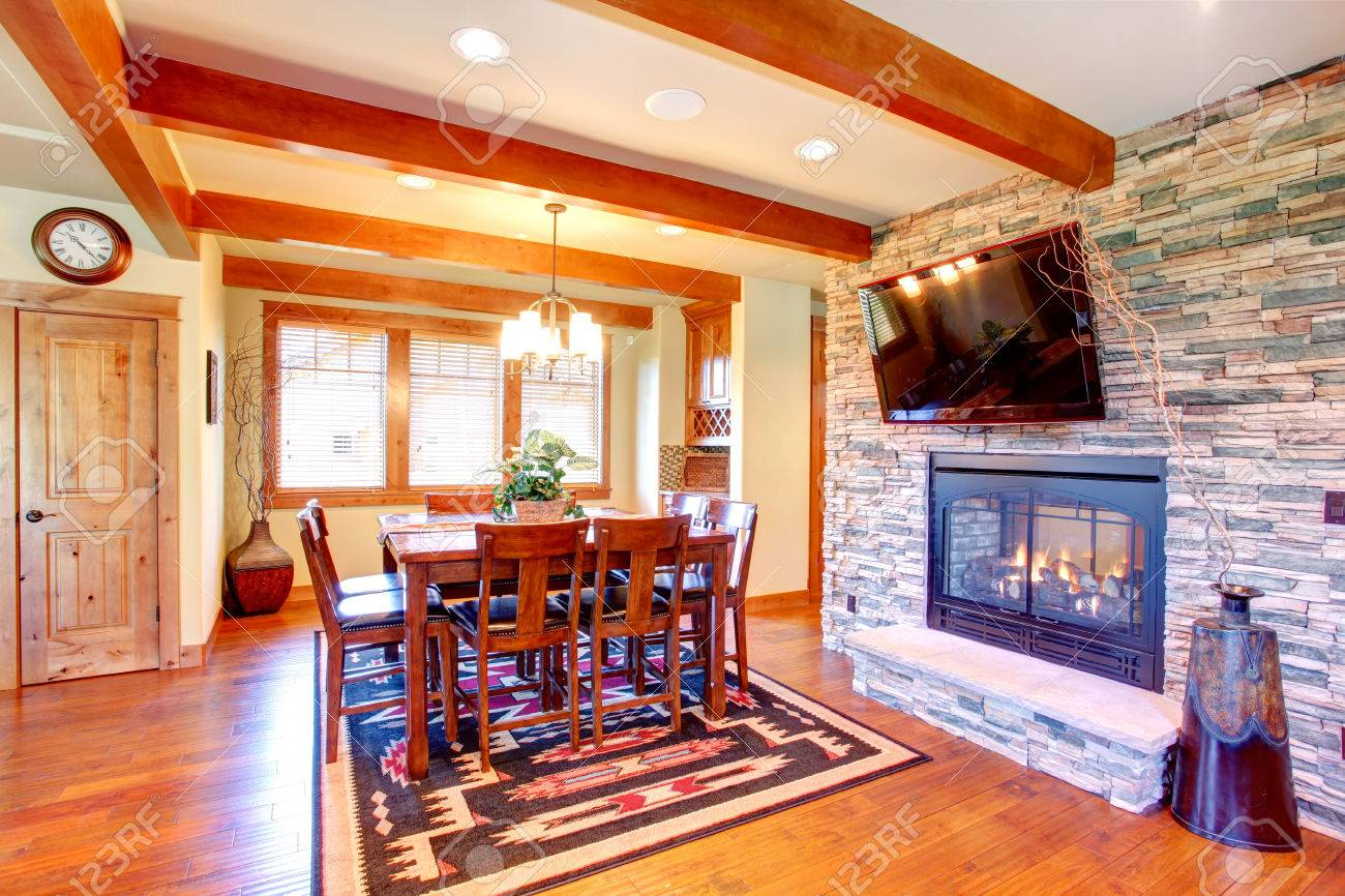 dining room interior celing beams blend perfectly with stone wall trim and fireplace dining room has