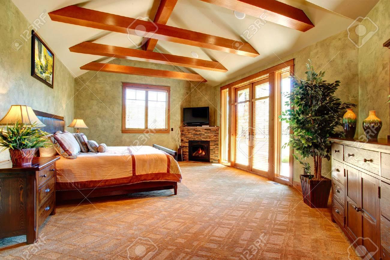 schönes schlafzimmer von licht grüntönen mit deckenbalken und stein