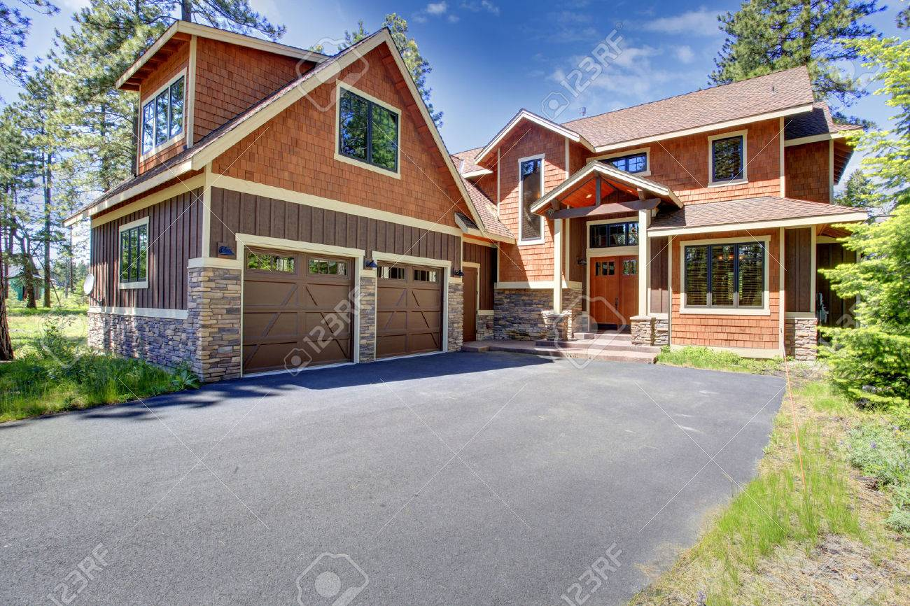 Big Luxury House With Brown And Orange Siding Trim. View Of Entrance Porch  And Two