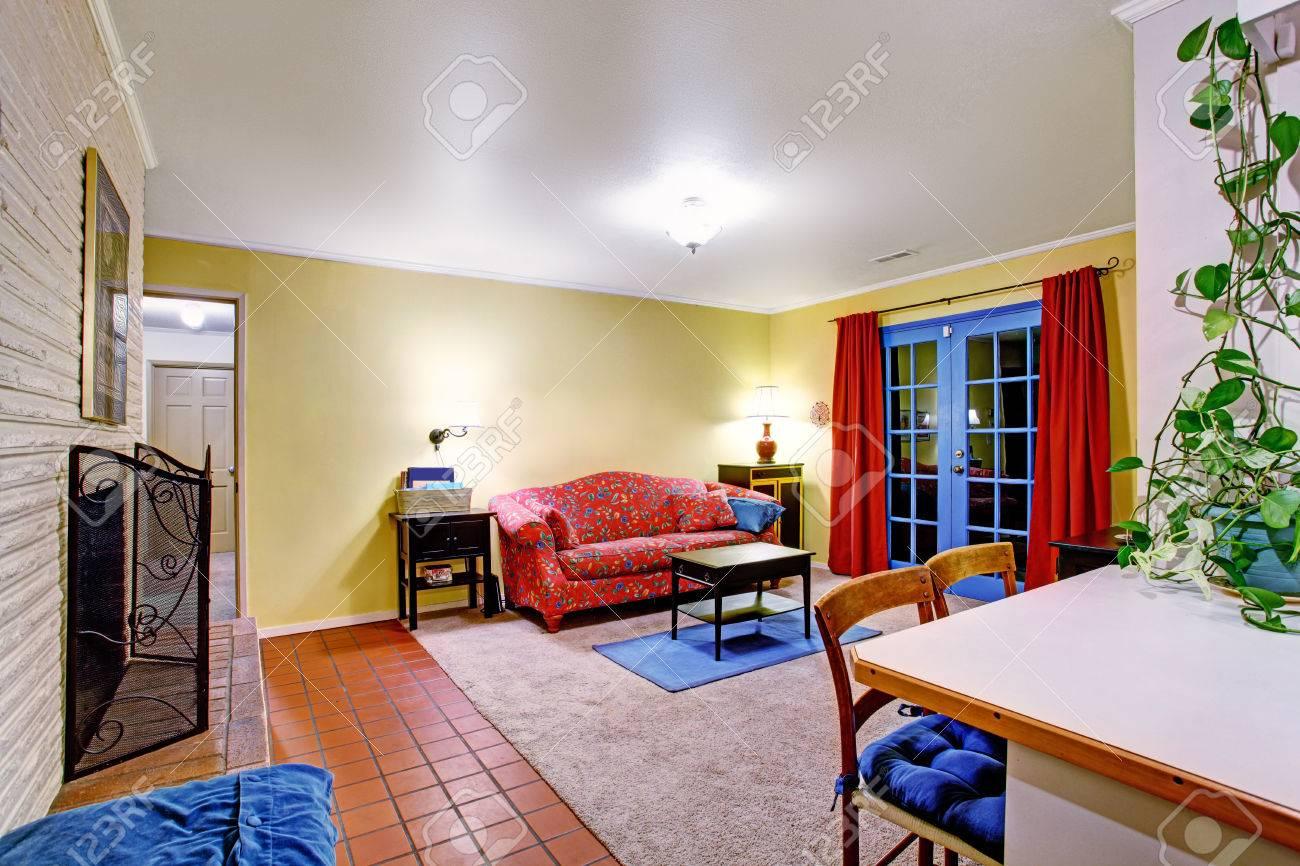 Heldere kleuren contrast woonkamer met rode sofa, kleine zwarte ...