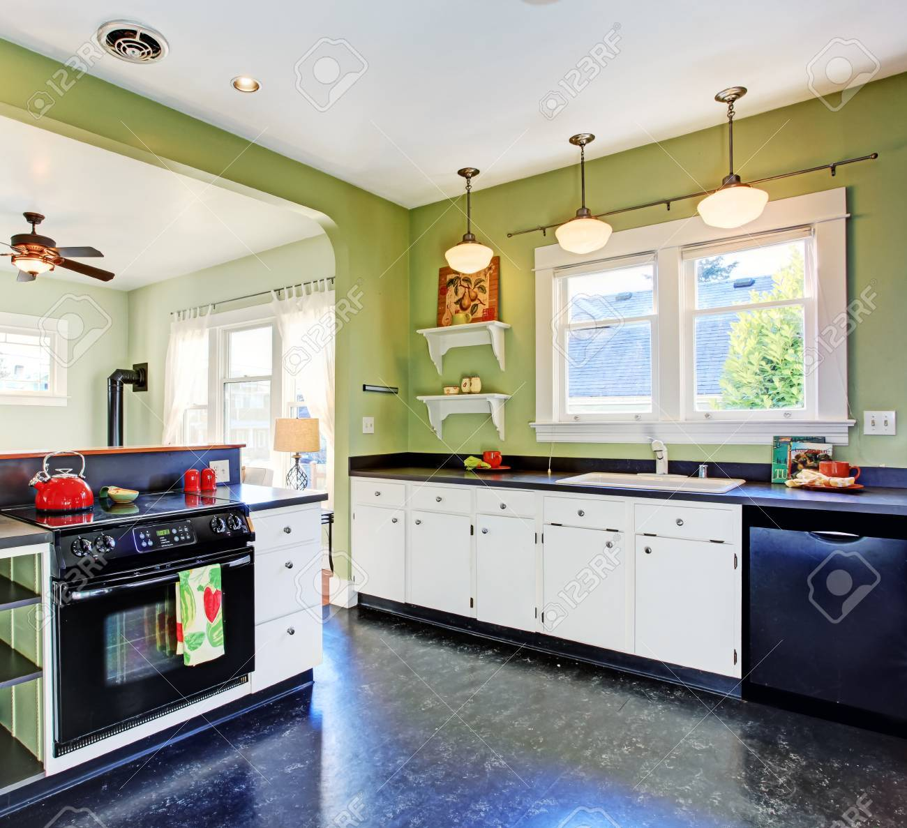 Kitchen Room With Green Walls White Cabinets And Black Appliances