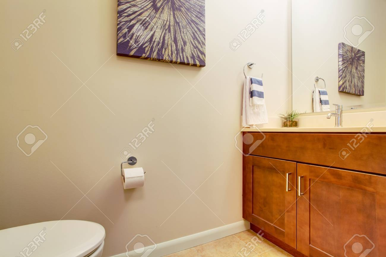 Simple bathroom corner with brown wooden vanity and toilet view Stock Photo - 28082804
