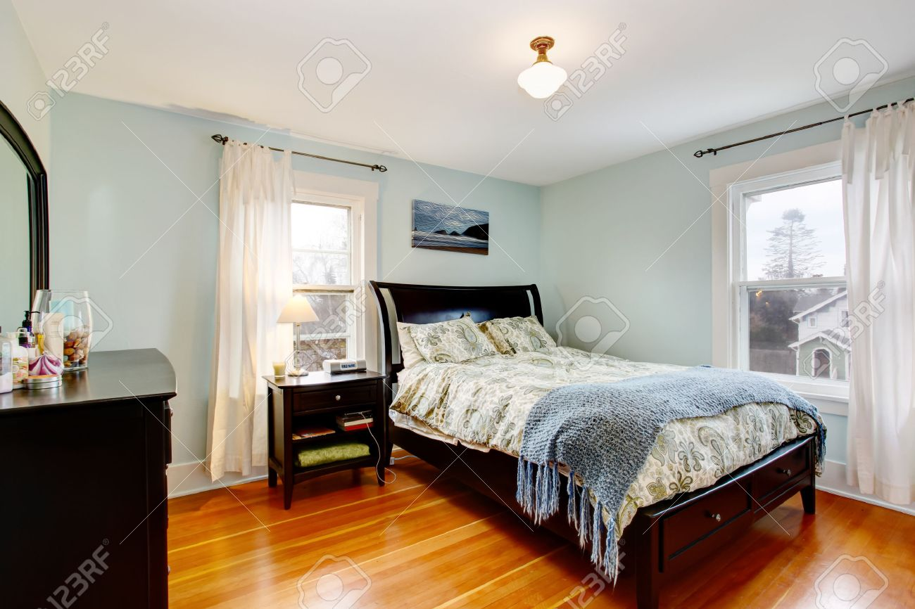 1394e4e85e5f Lgiht blue bedroom with two windows and hardwood floor Furnished with black  furniture set Stock Photo