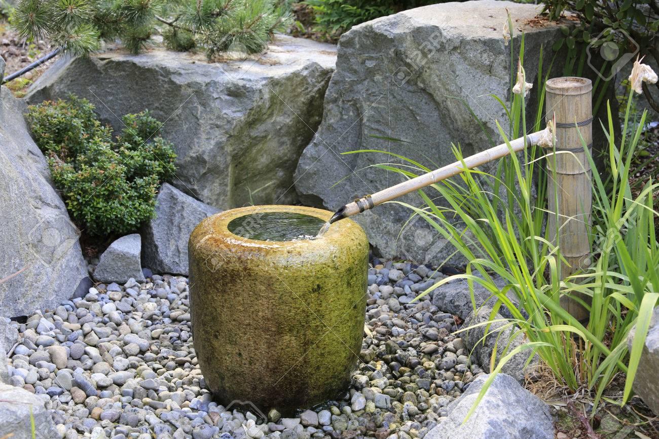 japanischen stil pumpe brunnen. wasser läuft aus einem bambusrohr in