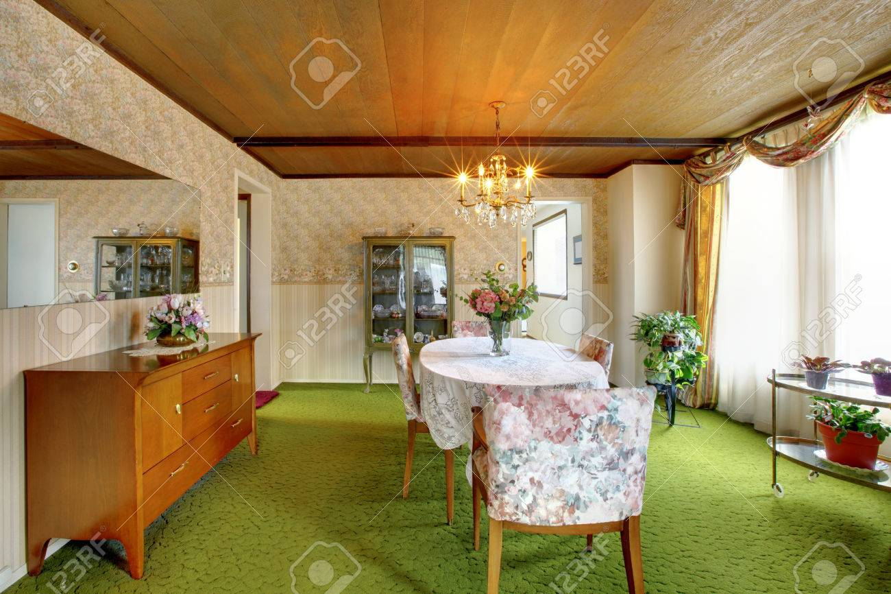 ... Dining Table Set. Old Fashioned House Interior With Antique Cabinets,  Green Carpet Floor, Wood Plank Paneled Ceiling
