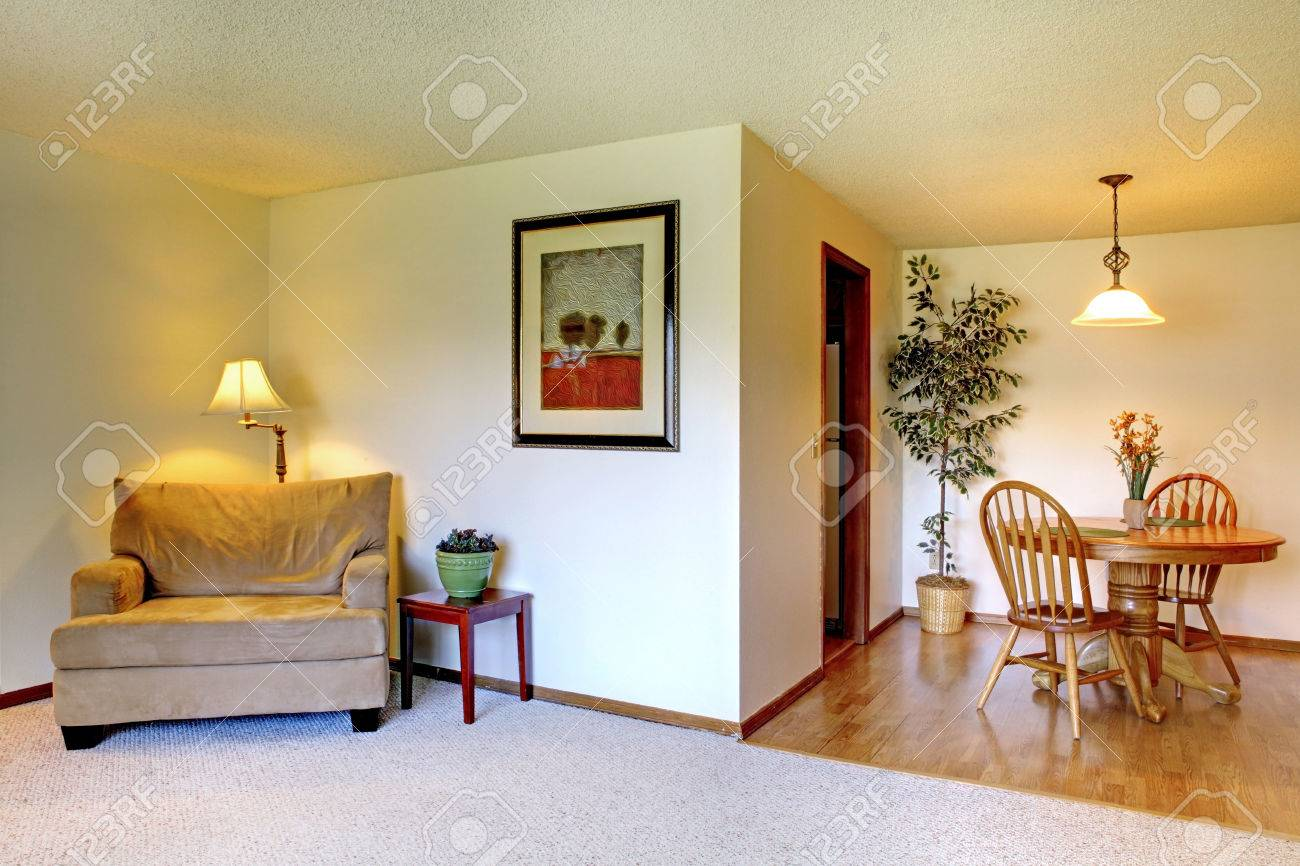 Living room with dining area decorated with fake tree and wall..