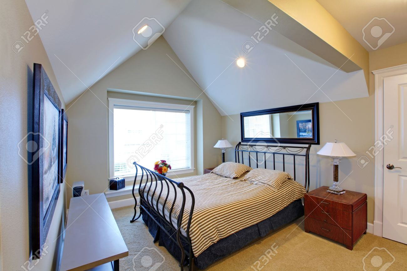 Small Bedroom With Vaulted Ceiling, Carpet Floor. Furnished With Metal  Frame Bed And Nightstand