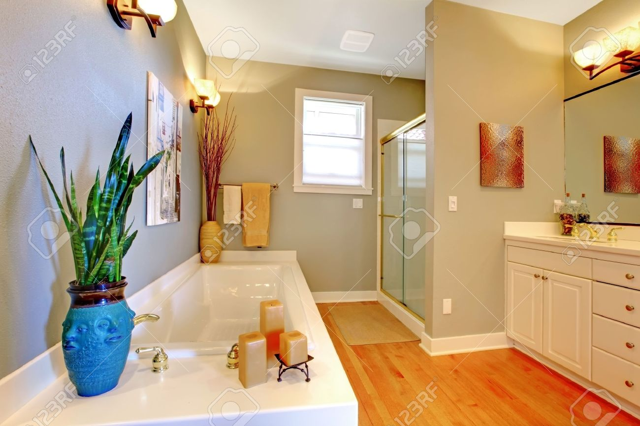 Salle de bains design d\'intérieur avec des murs verts et plancher de bois  franc. Vue de baignoire décorée avec des bougies et vase