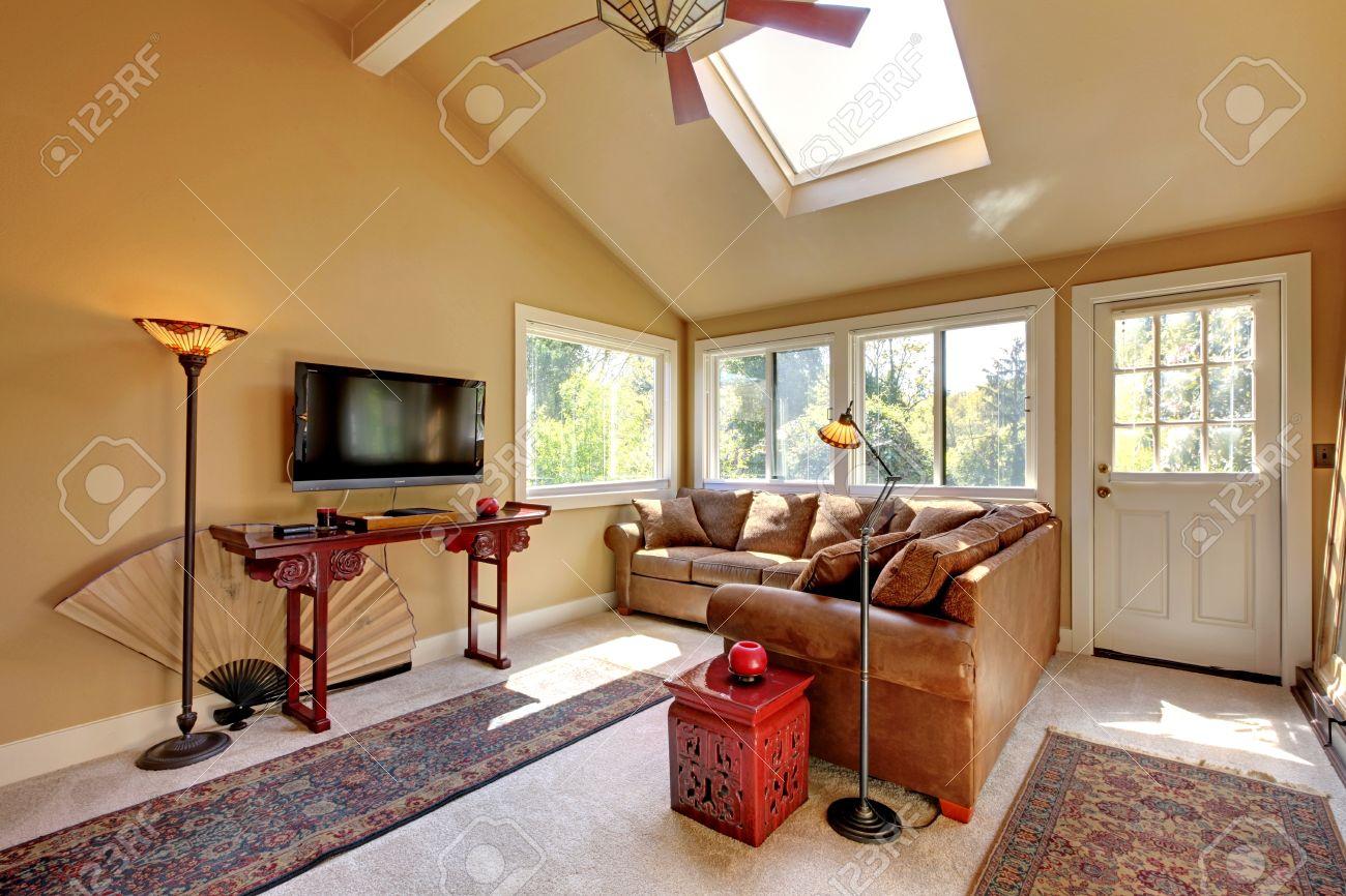 Grote woonkamer met een bank, tv en bruine muren met beige ...