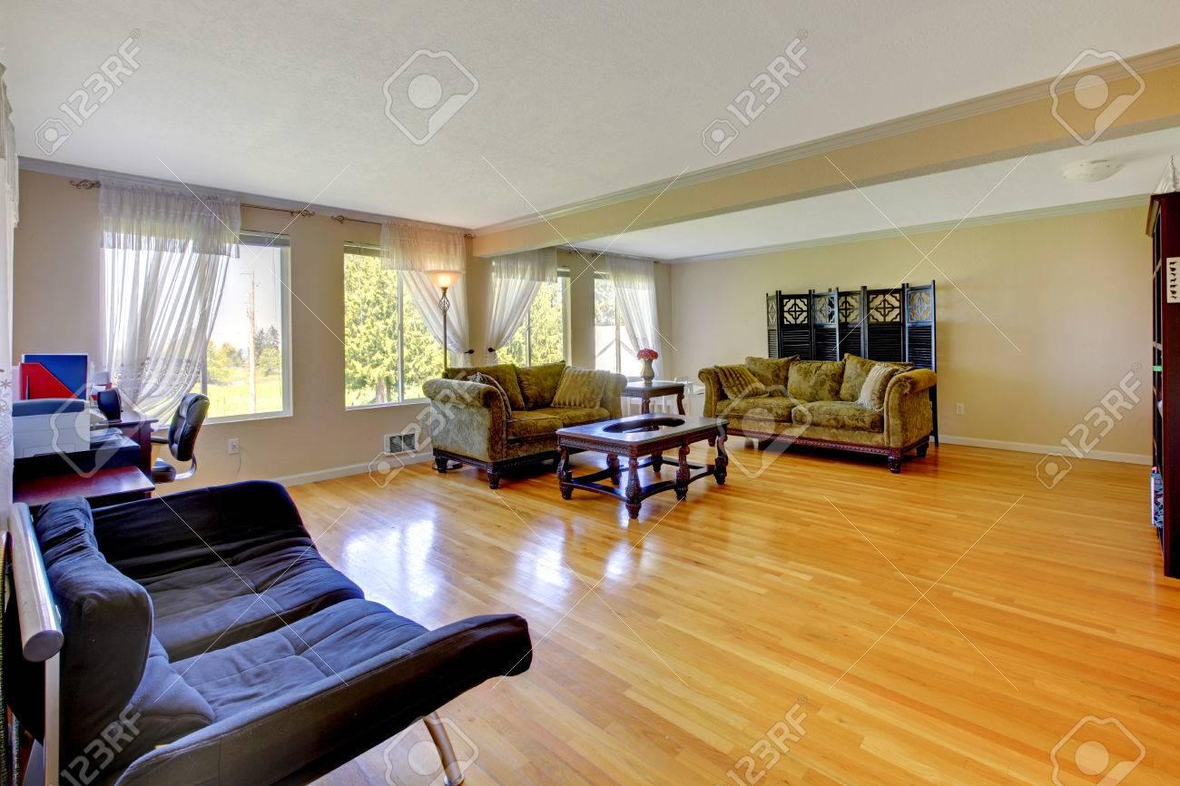 Table Basse Grand Salon grand salon avec plancher de bois franc, canapés verts anciennes, table  basse woode et coin bureau