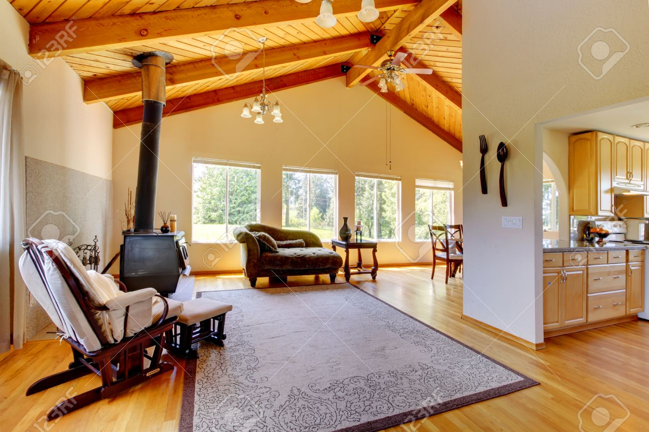 living room with high vaulted celing with beams room furnished with antique stove sofa and