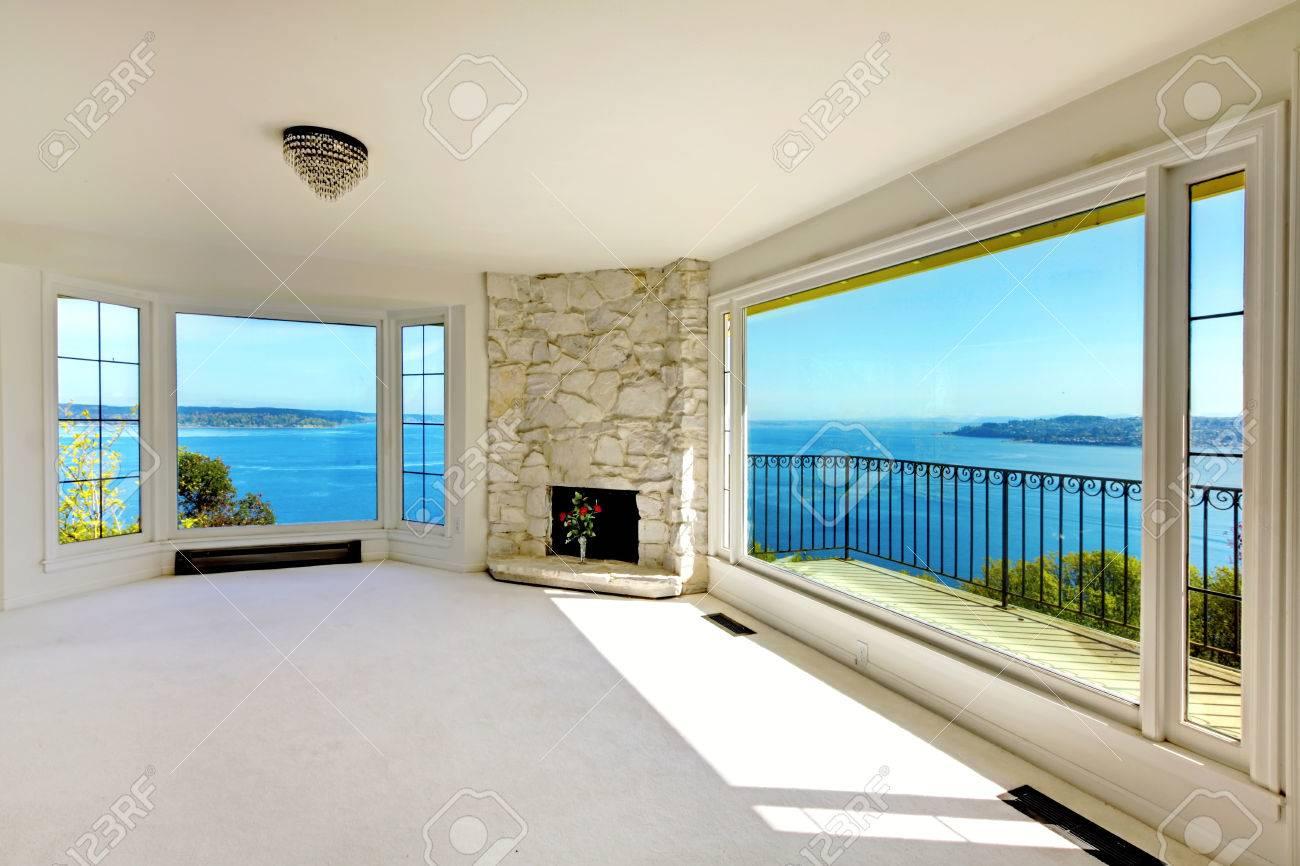 Immobiliën lege kamer met uitzicht op het water en open haard