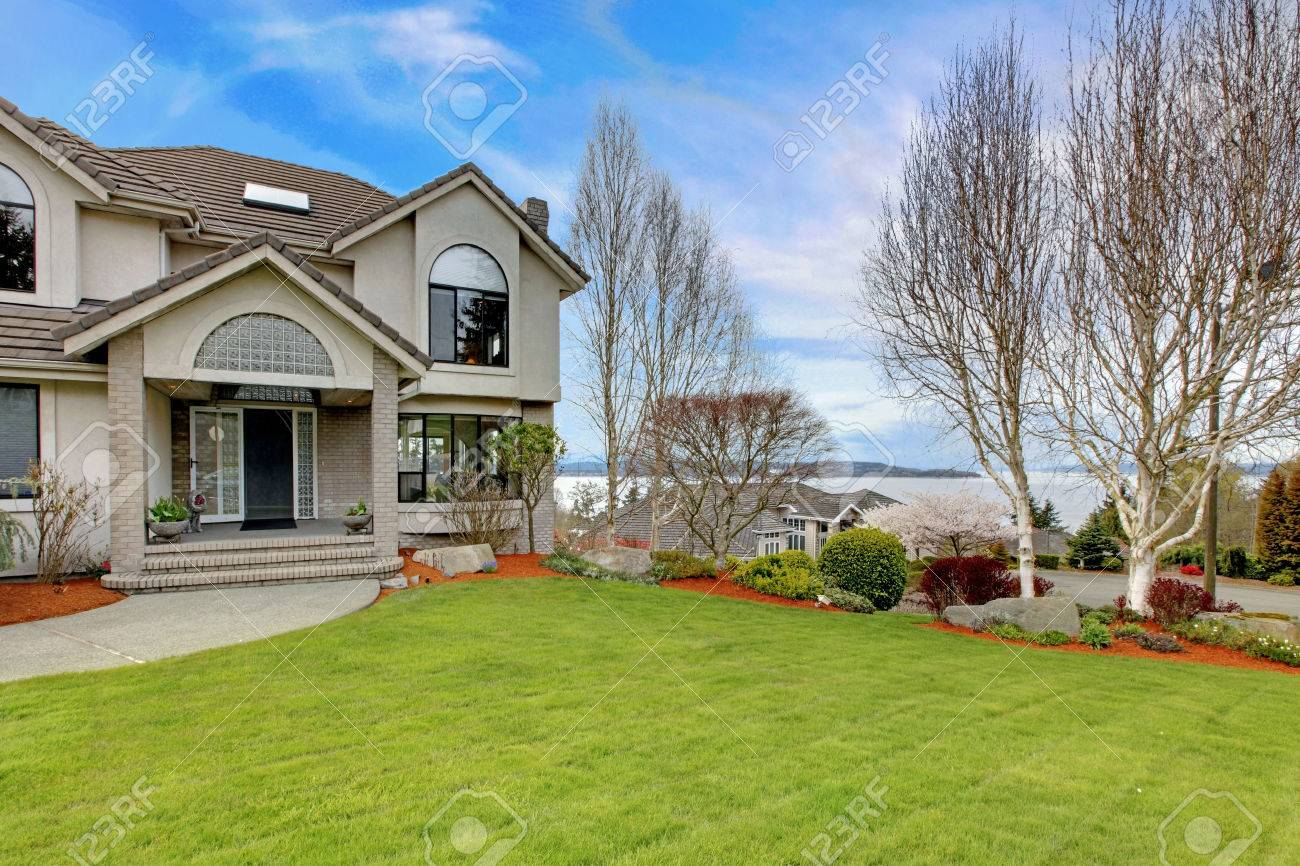 Luxury House Exterior luxury house exterior with flower beds and lawn. water view stock