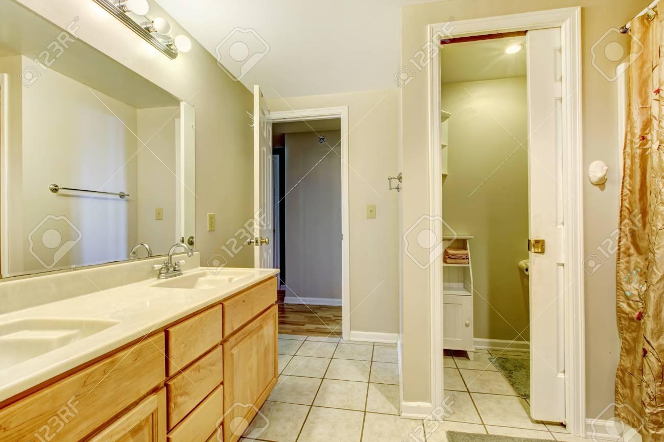 Bagno vuota con pavimento di piastrelle e vanità con lo specchio