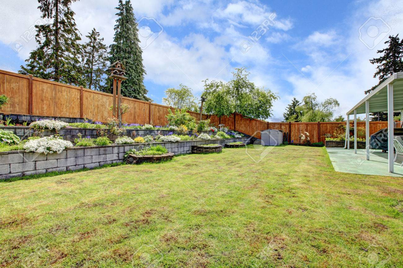 Fenced Backyard With Lawn Terrace Flower Beds And Porch With