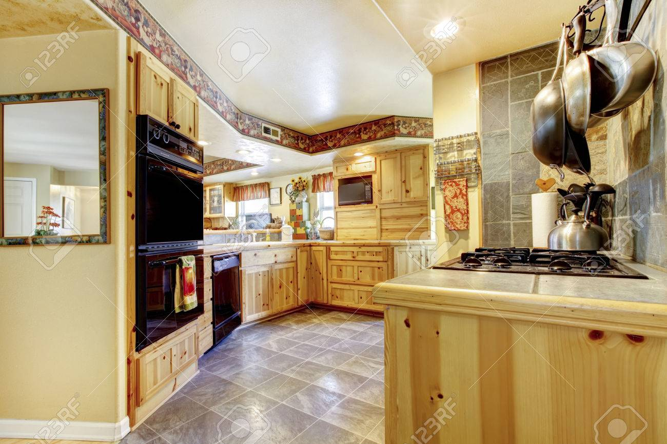 Rustic Kitchen With Gold Wooden Cabinets Black Appliances And