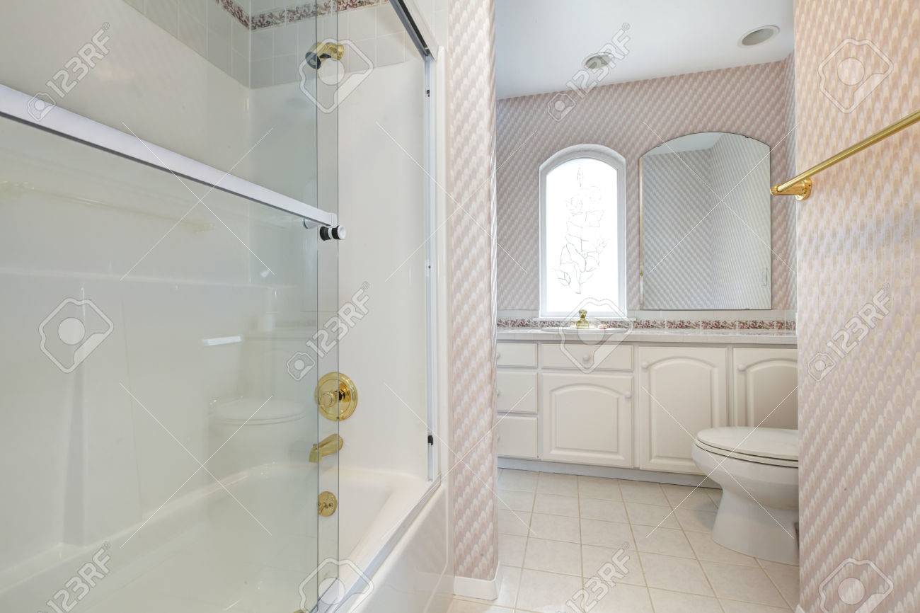 Refreshing Bathroom With White Cabinets, Toilet And Glass Door ...
