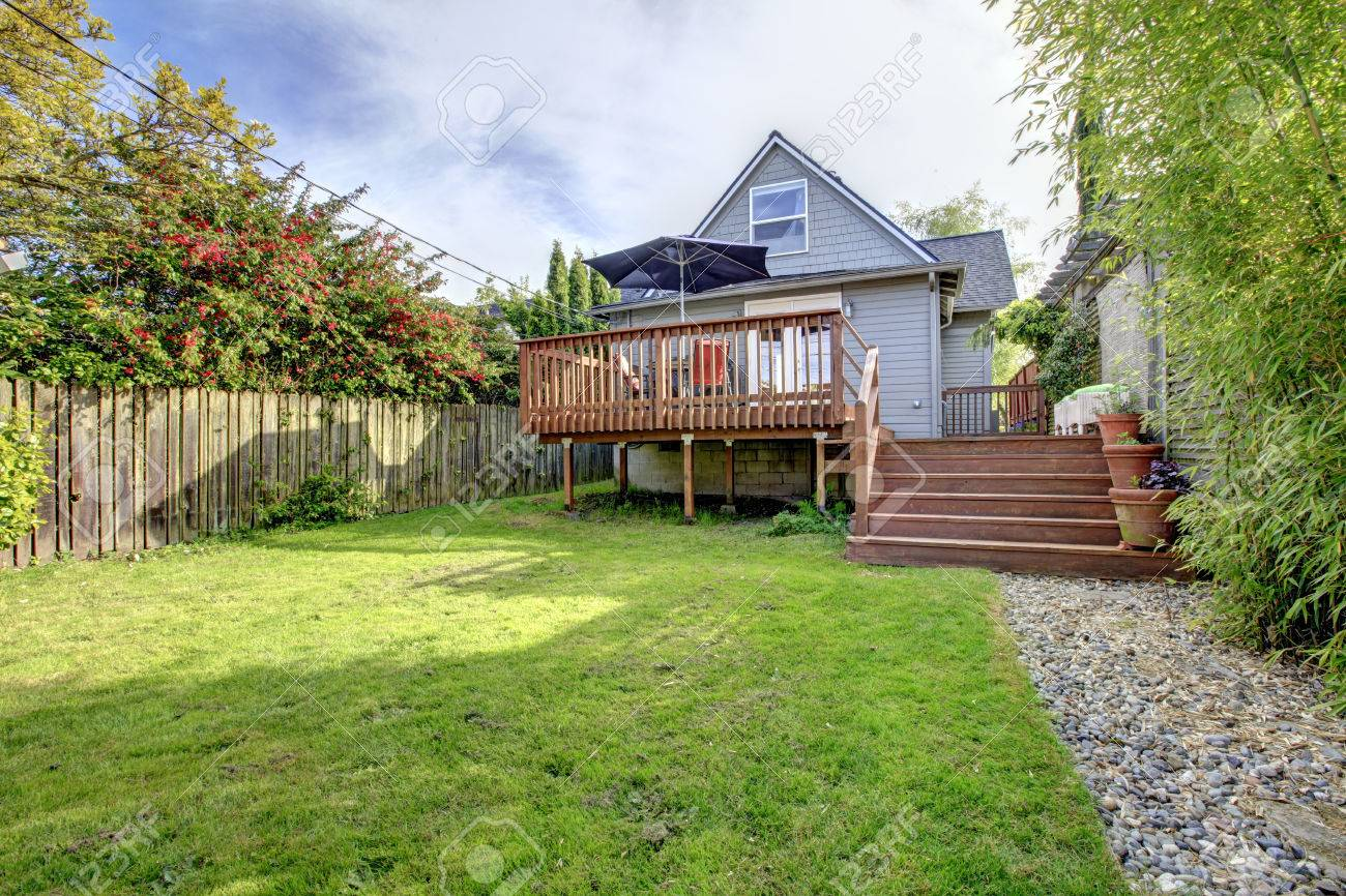 small house with walkout deck to backyard view of wooden deck