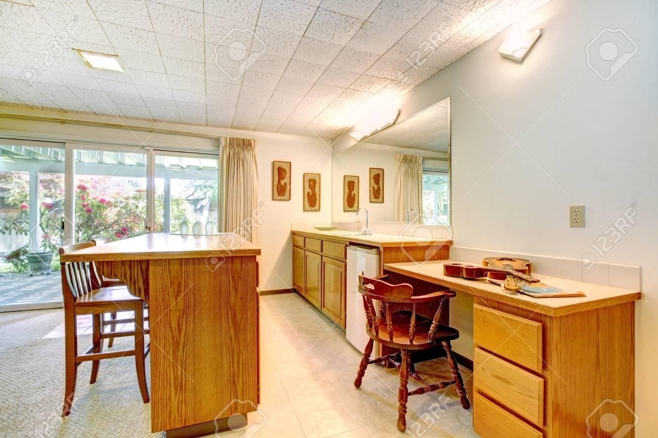 Amplio salón comedor con terraza de huelga. Vista de la barra de armarios  con taburetes, mueble con lavabo