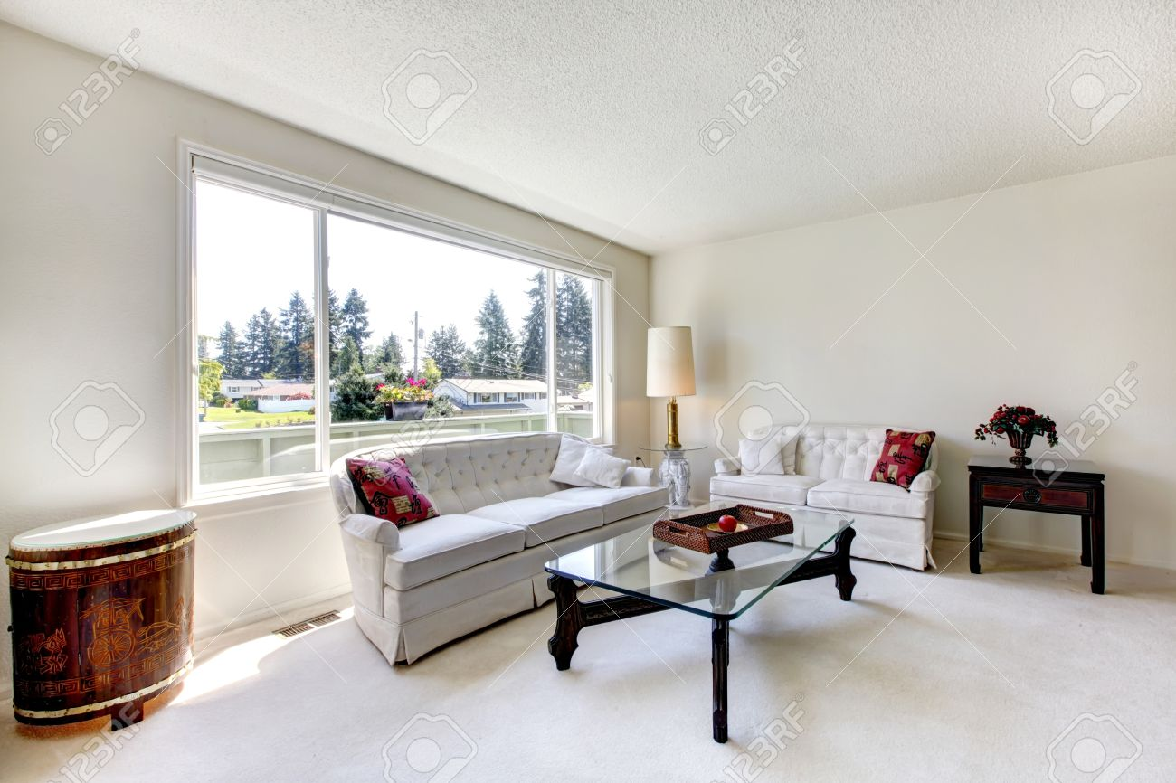 Bright living room with white carpet floor and furniture set view of glass top coffee