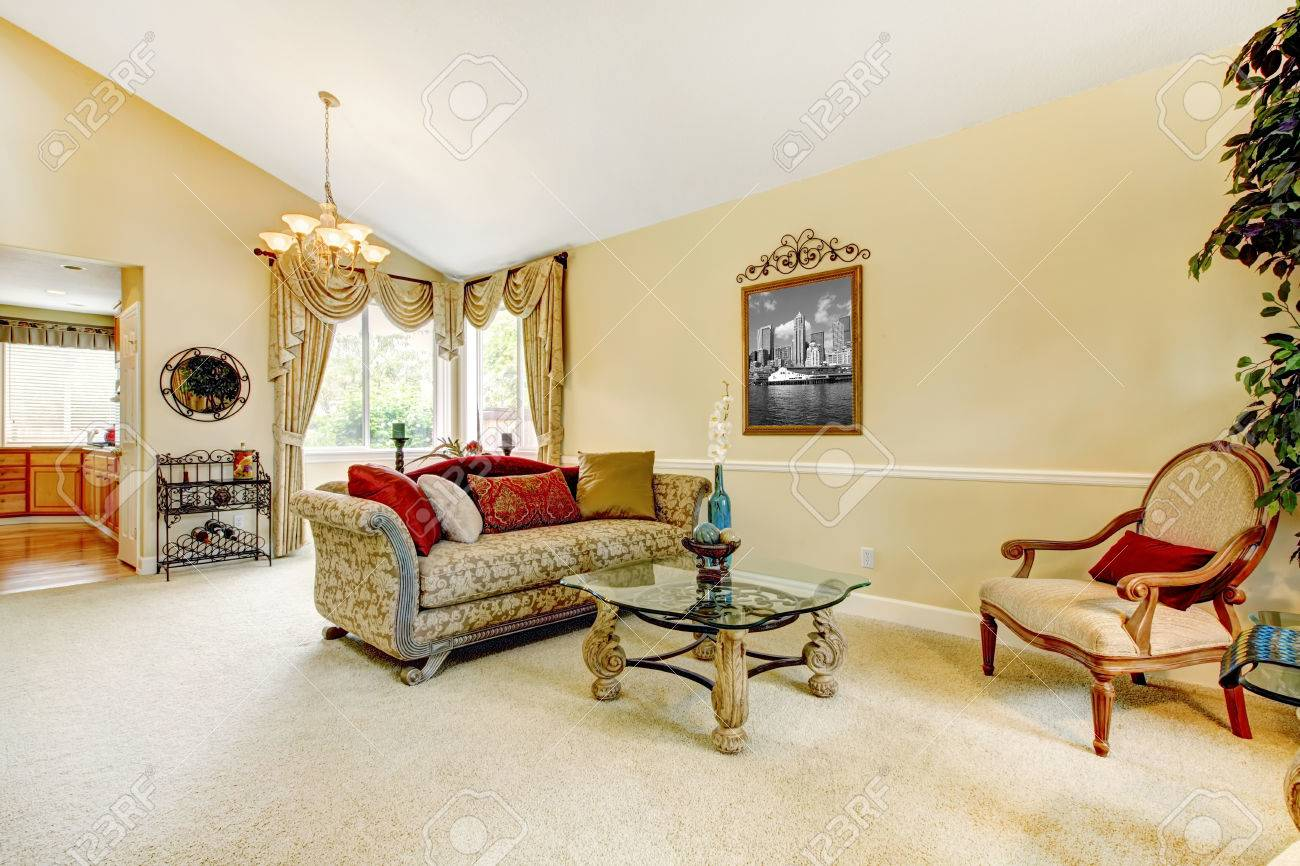 Spacious Ivory Living Room With High Vaulted Ceiling And Carpet Floor.  Furnished With Antique Sofa