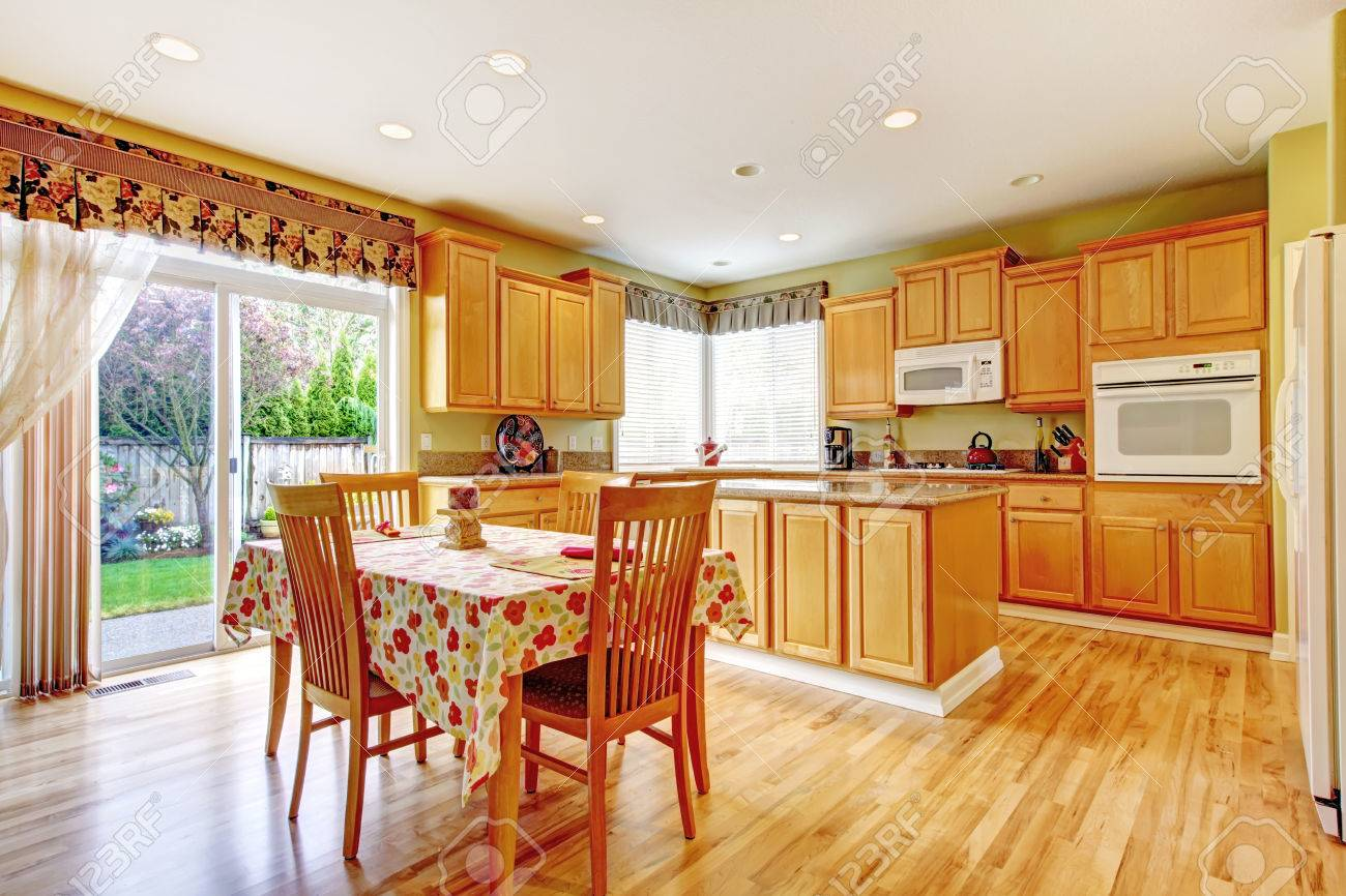 SImple yet practical kitchen interior. View of storage cabinets with kitchen island and dining area with walkout deck Stock Photo - 29378873