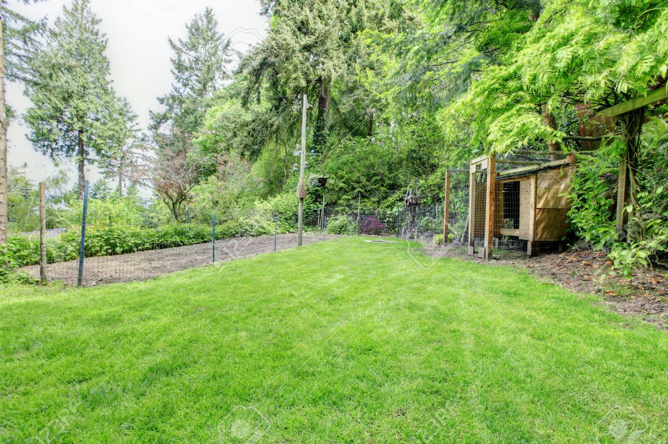 View Of Shed With Lawn And Fenced Garden Bed Stock Photo