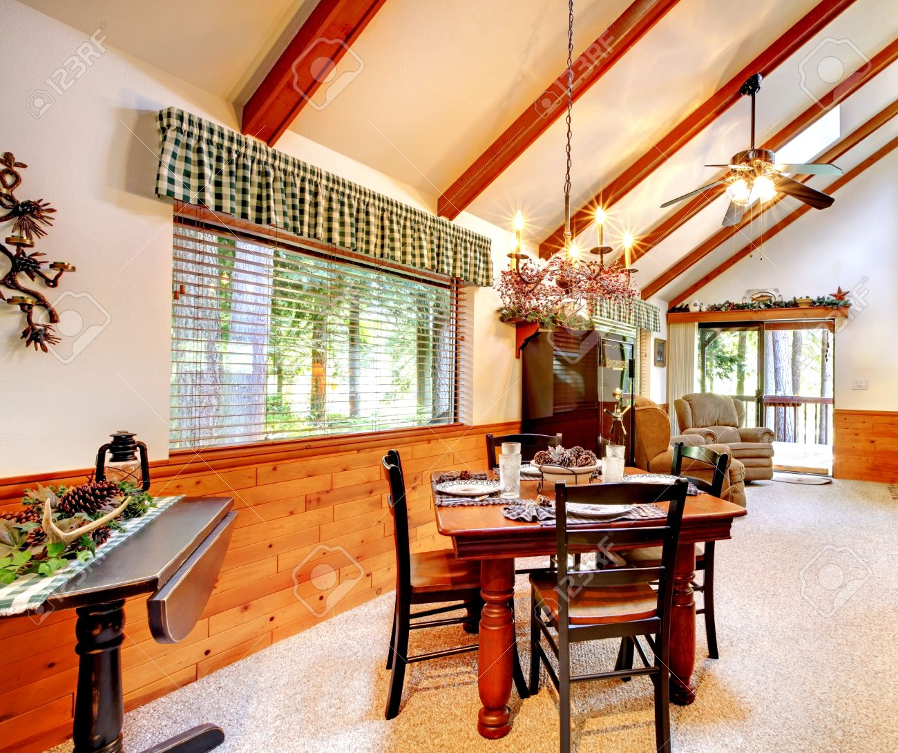 bright dining and living room in log cabin house high vaulted ceiling with beams and wooden