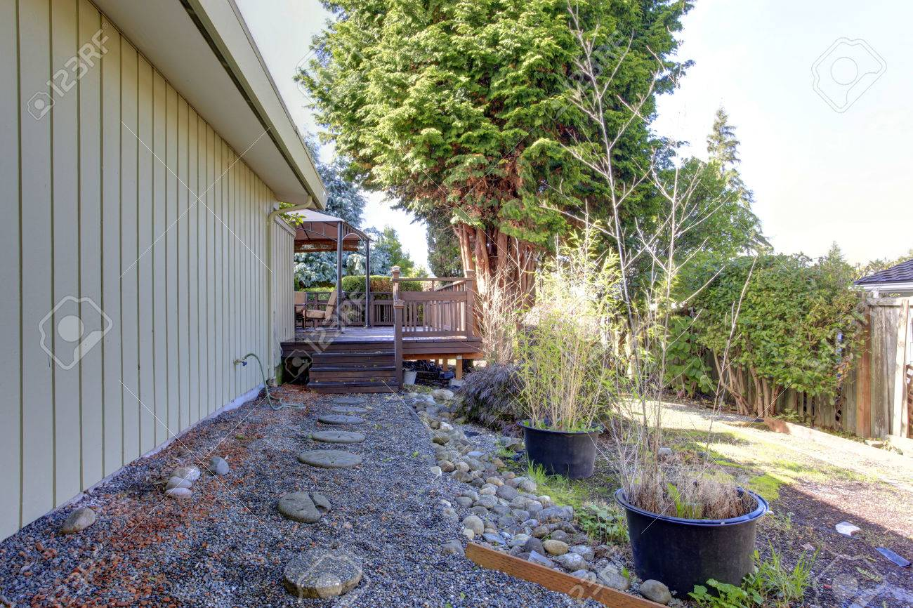 house with walkout deck and gravel walkway fenced backyard stock