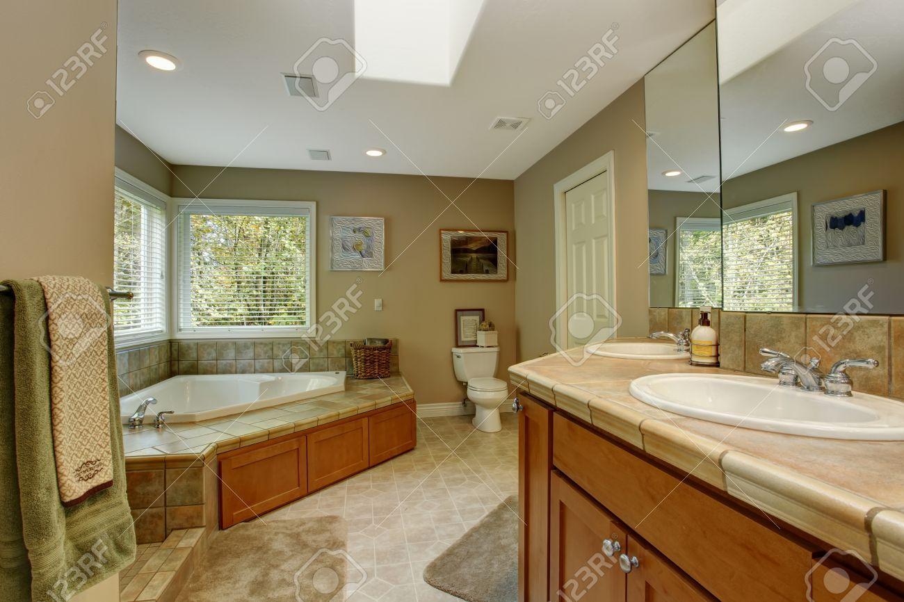 Amplio cuarto de baño con el ajuste de la pared de azulejos y bañera de  esquina. Vista del mueble de baño vanidad