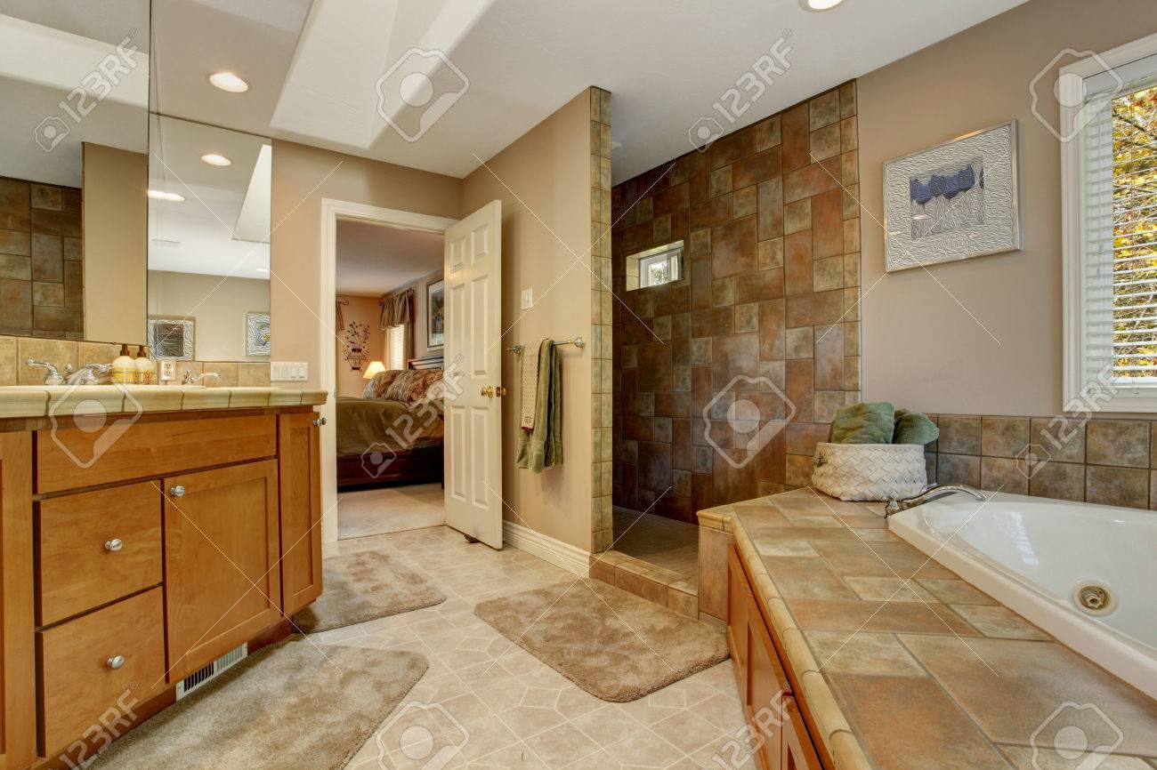 Spacious Bathroom With Tile Wall Trim And Corner Bath Tub. View ...