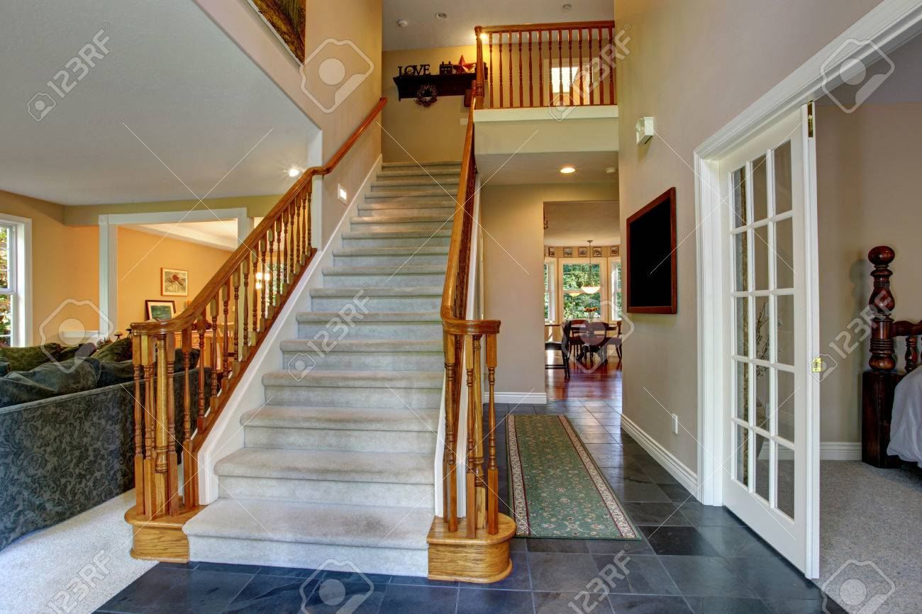 Spacious hallway with tile floor and staircase with wooden spacious hallway with tile floor and staircase with wooden railings stock photo 29666981 dailygadgetfo Gallery