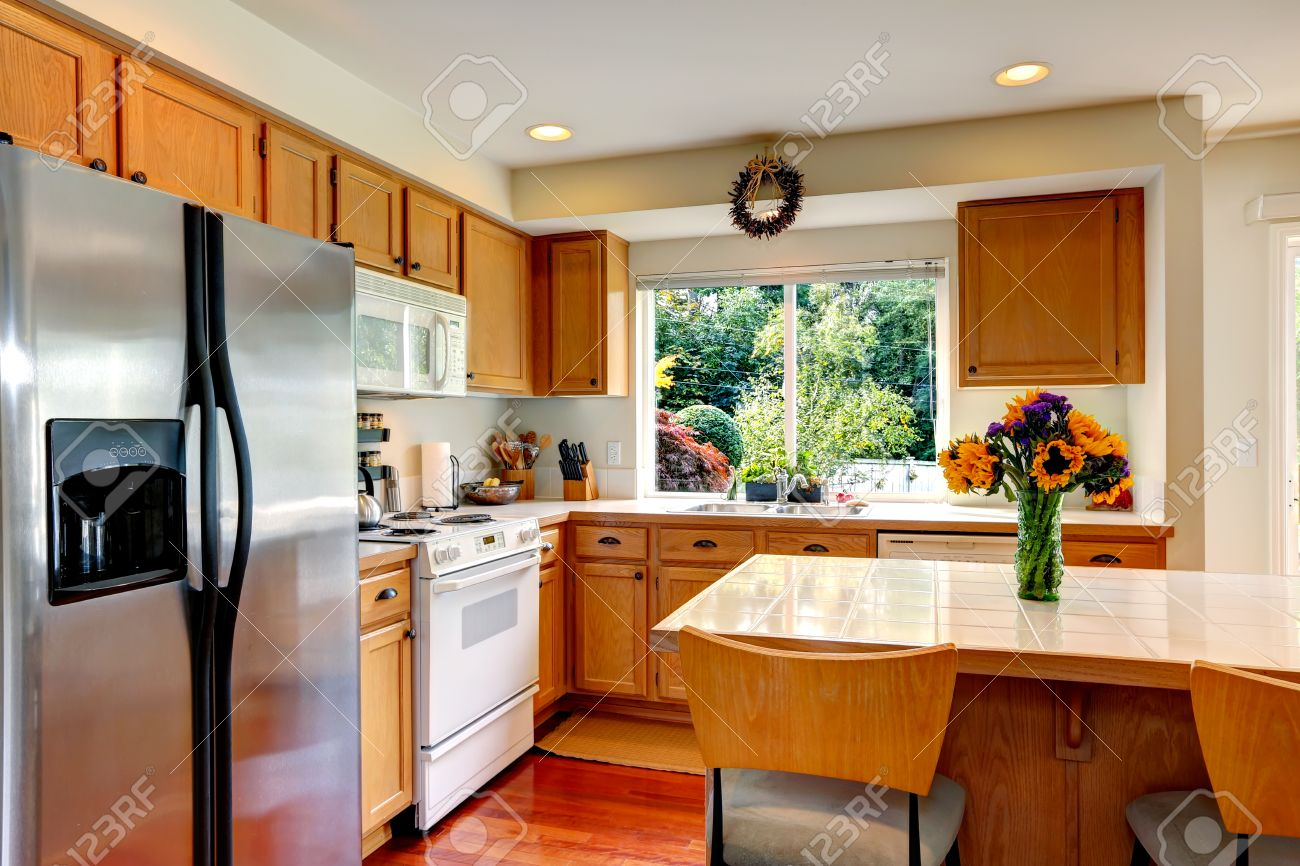 Cozy Kitchen With Honey Color Cabinets White Appliances And Island Fresh Flowers Stock