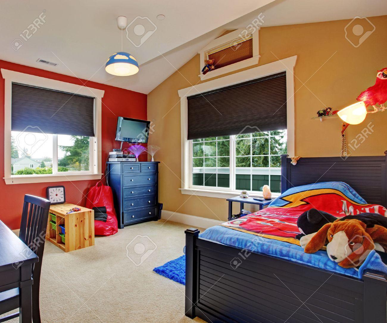 Colorful chambre des enfants avec des murs beige et rouge. Meublé avec un  lit simple et un bureau