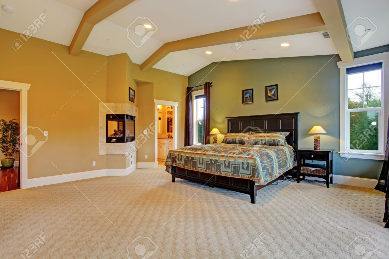 Spacious Master Bedroom With High Coffered Ceiling Beige Carpet Floor And Fireplace Built In The