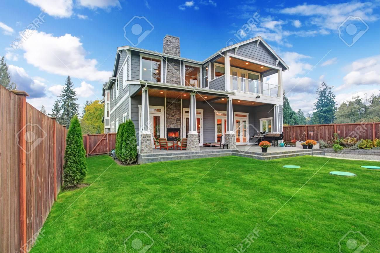 Casa De Lujo Con Terraza Paro Patio Trasero Y Porche Columna Vista De Césped Con árboles Y Macetas