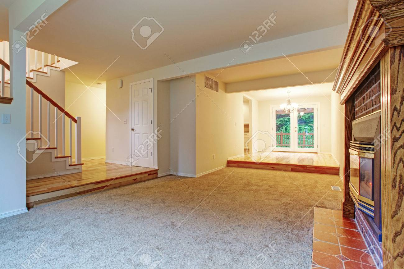 Empty living room with carpet - Empty Living Room With Carpet Floor And Fireplace View Of Hallway With Staircase Stock Photo