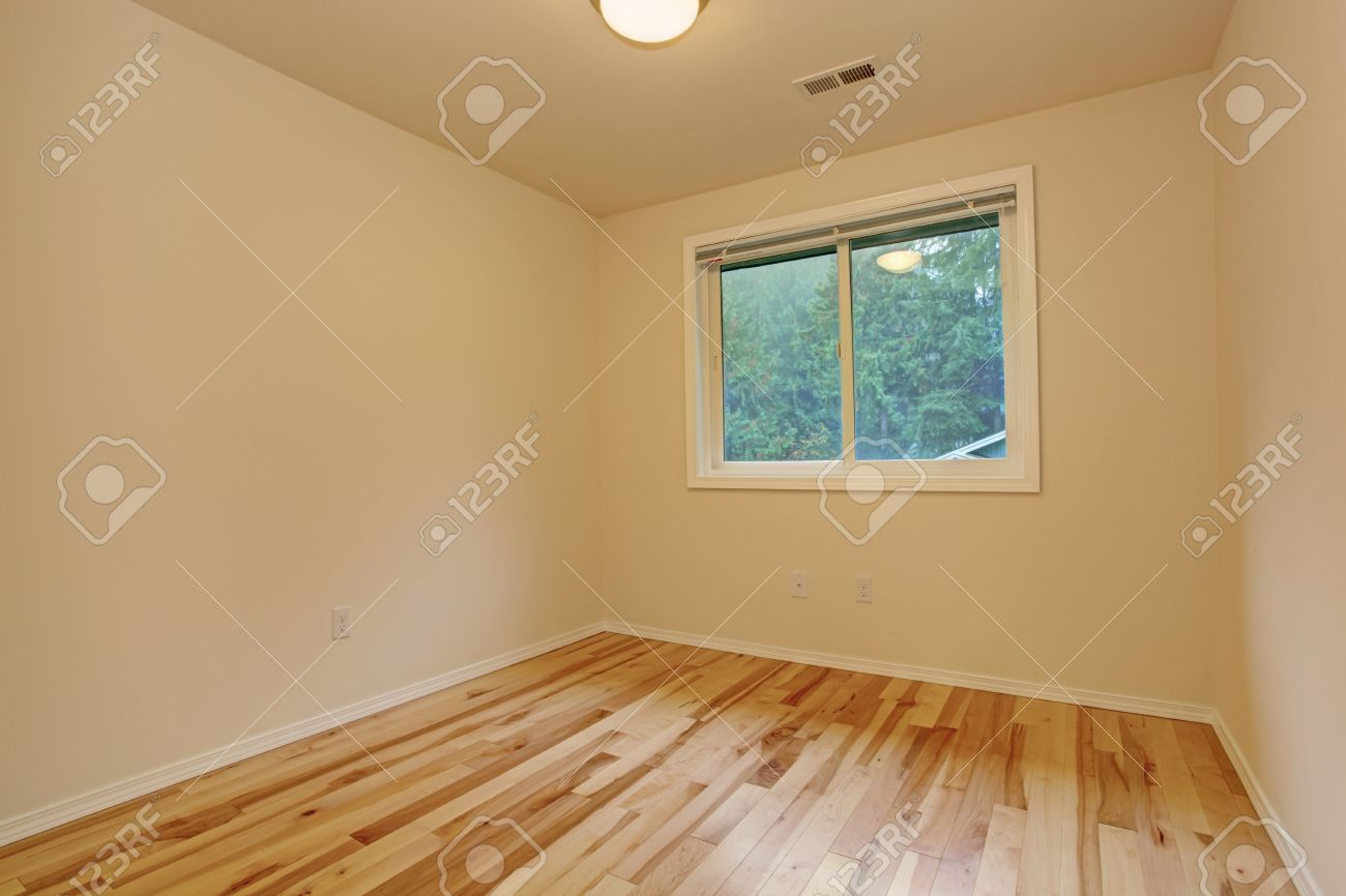 Small Empty Bedroom With Ivory Walls And New Hardwood Floor Stock