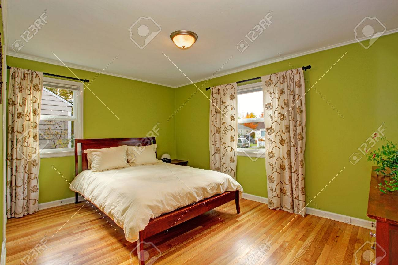bedroom with hardwood floor, bright neon green walls and wooden
