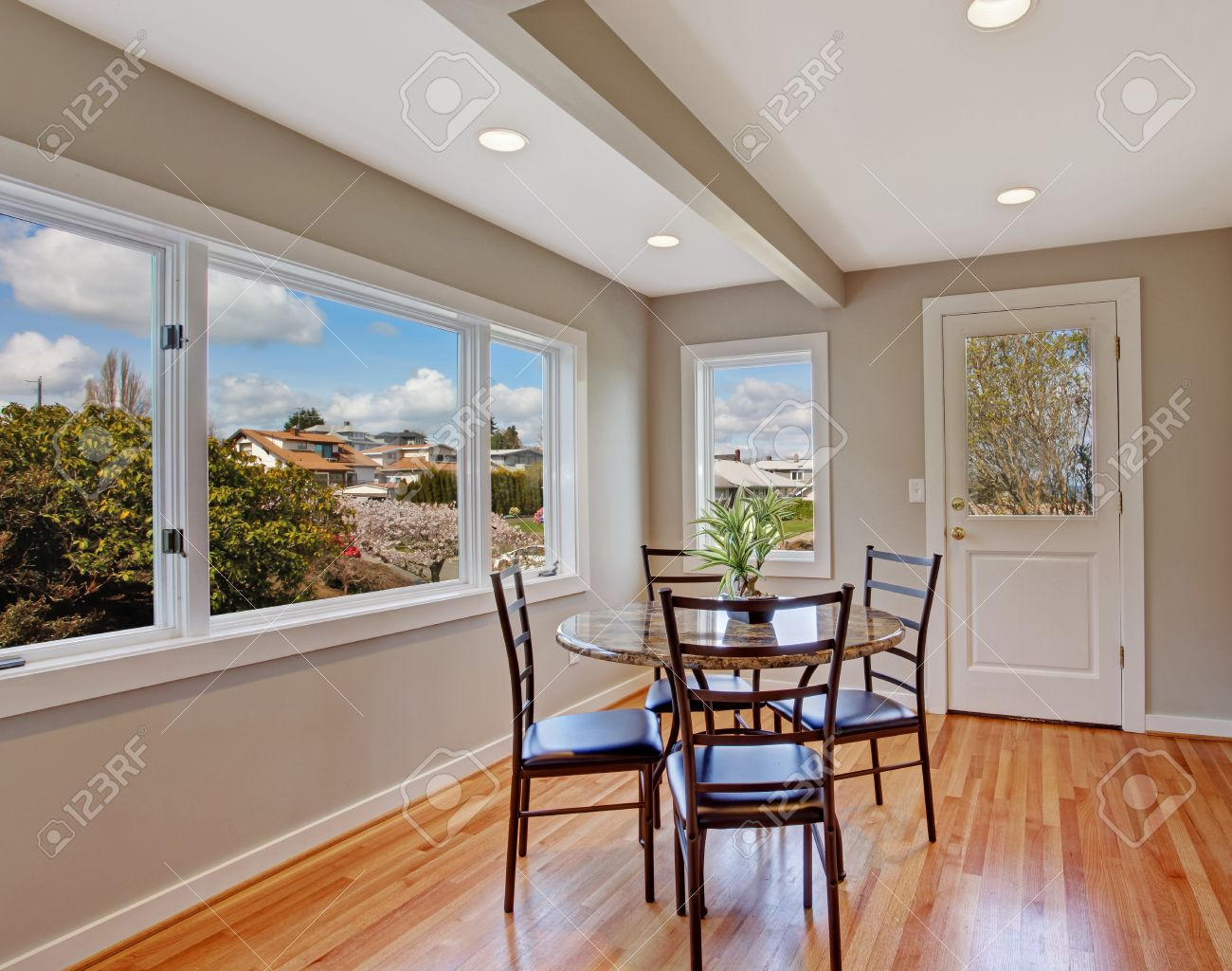 Attractive Bright Dining Room With Shiny Hardwood Floor And Light Grey Walls. View Of  Dning Table