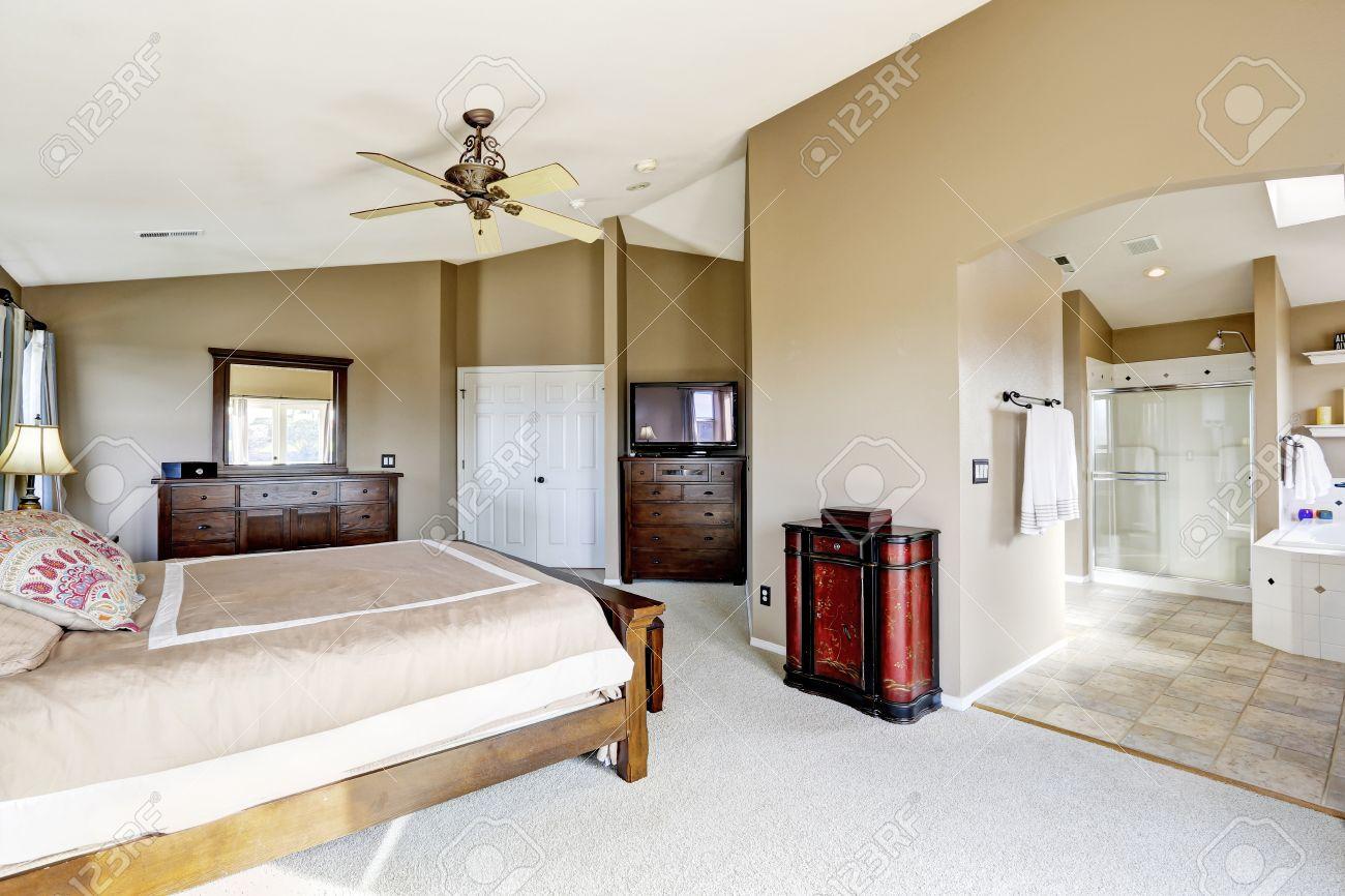 Luxe intérieur chambre avec salle de bains maître lumineux. Vue de lit avec  meuble-lavabo de la chambre, TV et commode
